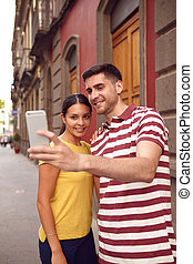 Happy couple taking a selfie in a old street - Young couple...