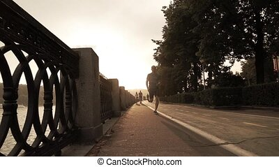 Man running on summer sunset embankment, Moscow. - Man in...