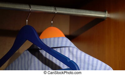 Taking a shirt from a wardrobe - Taking a blue shirt on a...