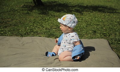 Cute playful smiled blond 1 years old boy sitting on green...