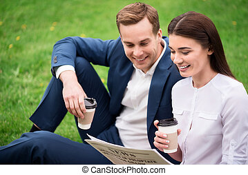 Positive colleagues drinking coffee on the grass - Just...
