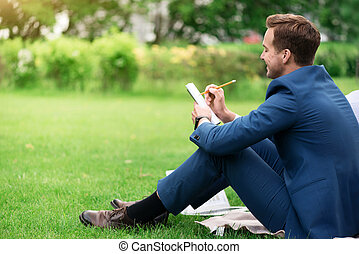 Positive delighted smiling man sitting on the grass - Keep...
