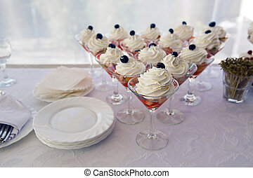 fruit glasses with cream and berries on top of blueberry...