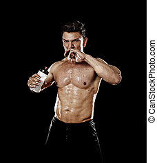 attractive strong sport man drinking water holding bottle...