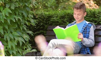 Teen boy reading book - Teen cute boy reading book sitting...