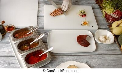 Knife cutting cooked meat. Plate with dark cooked pear....