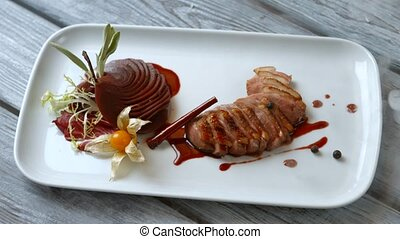 Pieces of meat with herbs. Cooked pear and meat. Duck breast...