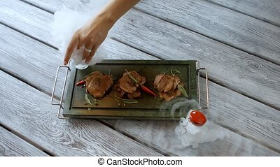 Pieces of meat on tray. Woman's hand puts small jar. Veal...