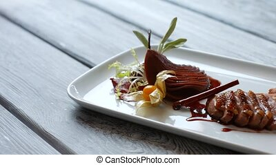 Cooked meat on white plate. Meat with herb and pear. Duck...