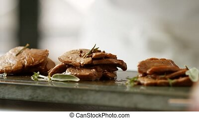 Hand puts pepper on meat. Brown meat and green herbs. Veal...