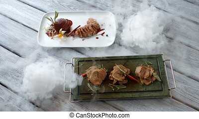 Cooked meat with herbs. Plates with slices of meat. Veal...