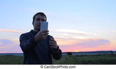 Man makes selfie on phone. Against the backdrop of a beautiful sunset sky