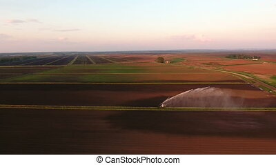 Aerial view:Irrigation system watering a farm field -...