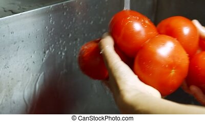 Man's hands wash tomatoes. Water flowing on huge tomatoes....