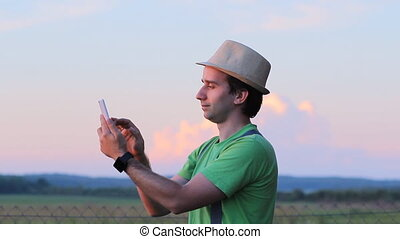 A man makes a video call on the phone. Against the backdrop of a beautiful sunset sky