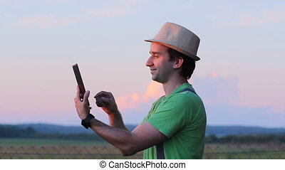 The man in the hat is touching the tablet. Against the backdrop of a beautiful sunset sky