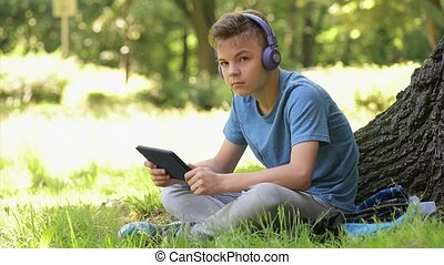 Boy with tablet at park - Happy teen boy 12-14 year old in...