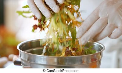 Hands mix salad. Salad with herbs in bowl. Shredded carrot...