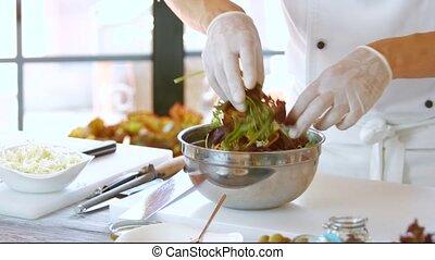 Male hands making salad.