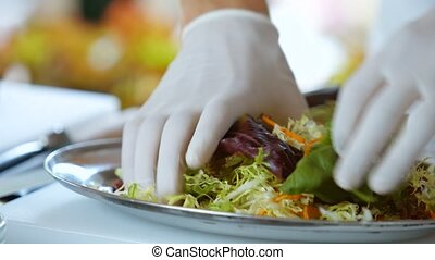 Hands in gloves mixing salad. Salad with fresh greenery....