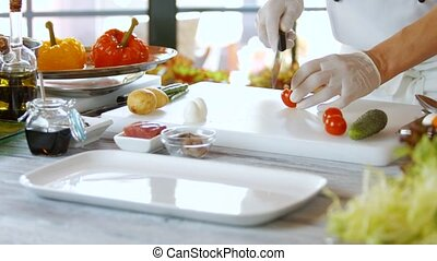Hands with knife cut tomatoes. Vegetables on cooking board....