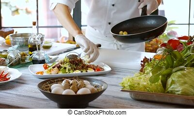 Hand puts potatoes on salad Small potatoes on frying pan...