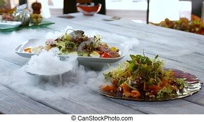 Plates with salads. Steam coming out of bowls. Roasted...