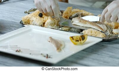 Spatula putting fish onto plate. Cooked fish on white plate....