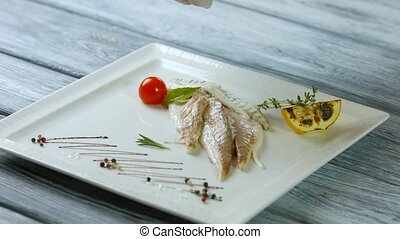 Liquid pours on cooked fish. Fish with lemon and herbs. Chef...