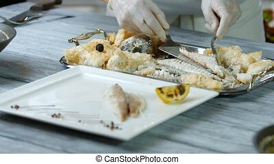 Spatula puts piece of fish. Plate with fish and lemon. Soft...