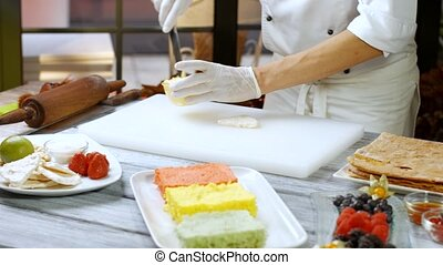 Spatula puts custard on shortcake. Man prepares dessert at...