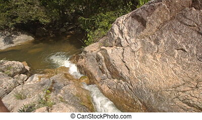 Camera Moves along Small Mountain River among Stones -...
