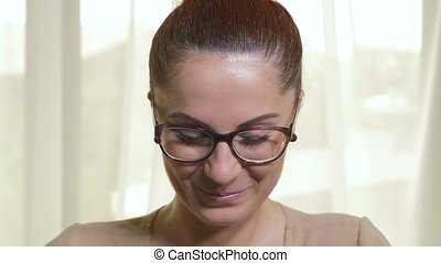 Young attractive woman with glasses flirting and blowing...