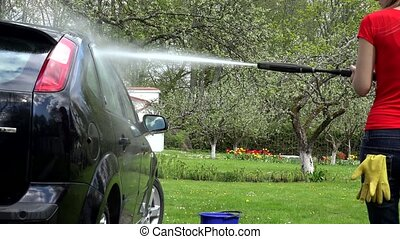 gardener woman washing her car with strong water jet in open...