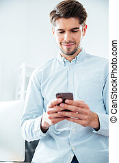 Happy attractive young man using smartphone in office -...