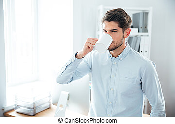 Handsome young man drinking coffee in office - Handsome...