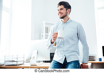 Happy businessman drinking coffee in office - Happy...