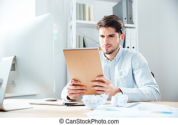 Handsome young businessman man sitting and reading notes in...