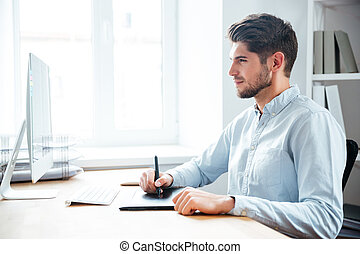 Man designer working using computer and graphic tablet in office