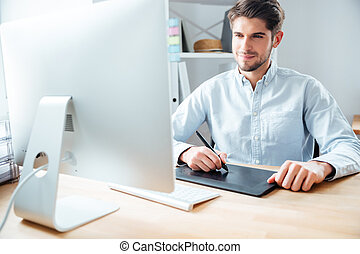 Man designer working using computer and graphic tablet at...