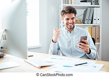 Happy young businessman using smartphone and celebrating...