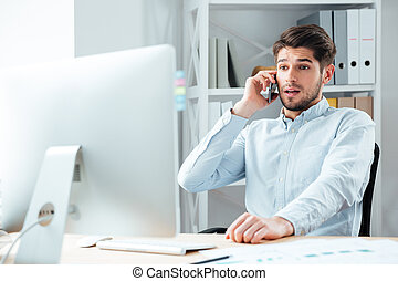 Portrait of surprised businessman talking on mobile phone in office
