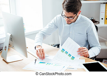 Handsome young businessman working with documents and...