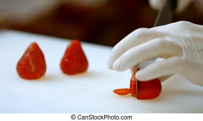 Hand with knife cuts strawberry.