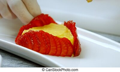 Hands touch strawberry slices.