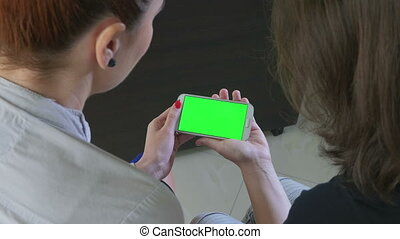 Two business women holding a smartphone with green screen