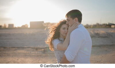 Young couple stand on  beach, embrace each other.