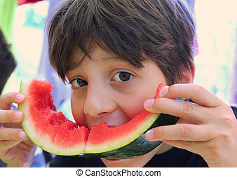 hungry boy eating a slice of watermelon - very hungry boy...