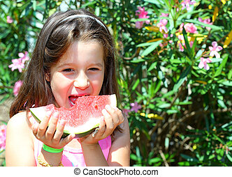 little girl with long brown hair eating a slice of ripe...