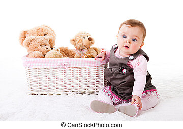 Toddler Sitting Next to Teddy Bears - A cute baby girl is...